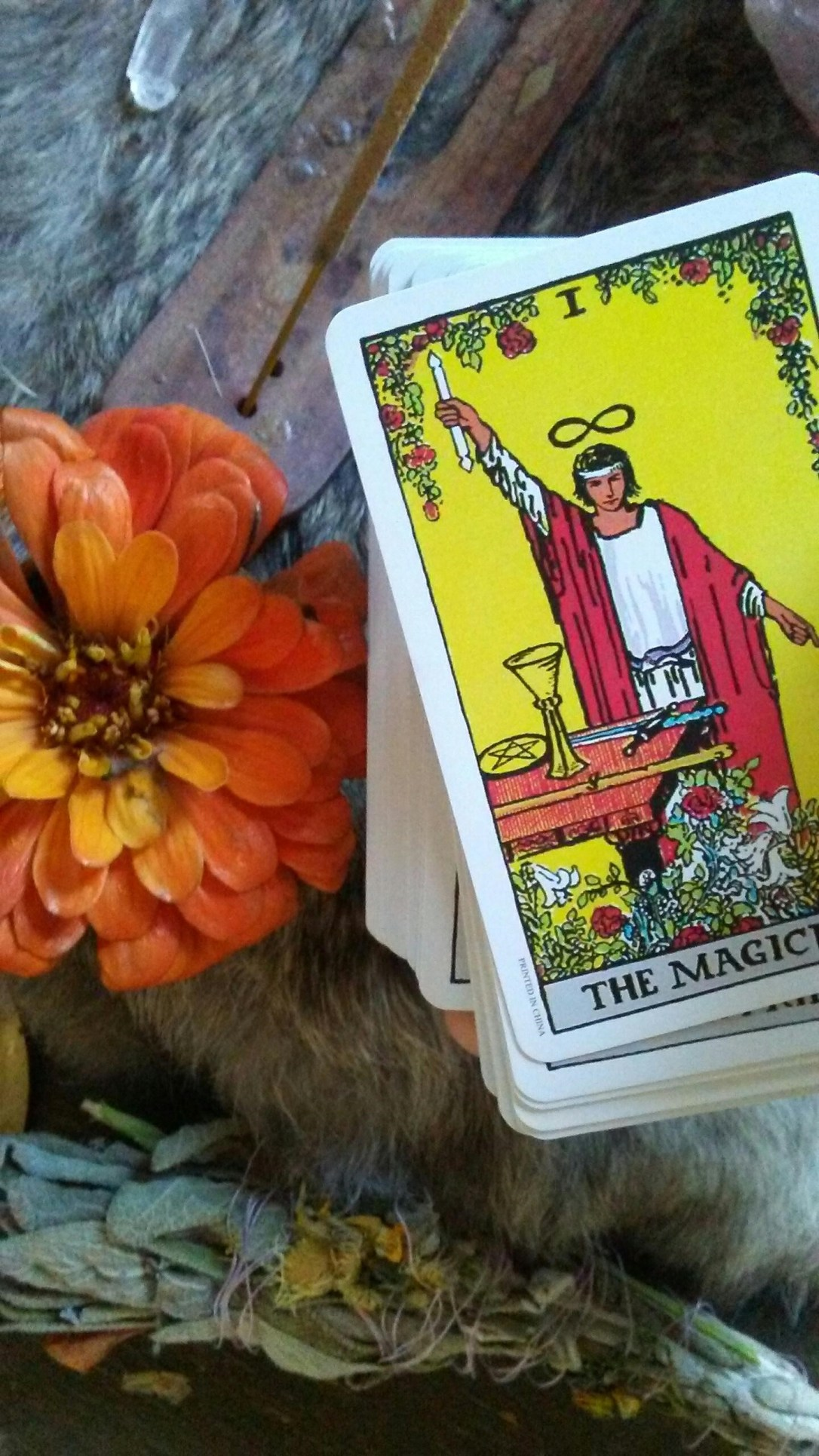 The Magician Tarot Card with incense, sage bundle, crystal, and orange flower.