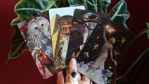 Hand holding handmade tarot cards with thumb ring