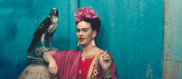 Frida Kahlo smoking a cigarette beside a hawk