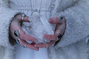 woman with rings on her fingers and thumbs holding a white crystal in winter