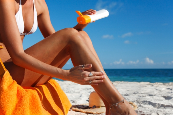 woman applying sunblock on her legs at the beach
