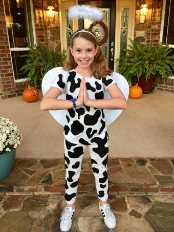 """Girl dressed in cow print clothes with wings and a halo """"holy cow"""""""