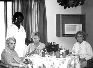 """(photo from left to right) Maxine Brown, Barb Woodfin (Dietary Manager), Rita Martin, and Betty Cunningham not knowing each other prior to coming, have become friends and do many of the activities and outings together. Maxine states, """"I have made some good friends, quite a lot of friends here at Riverbend. The nurses are nice, too."""" Indeed it has become these ladies' home and they, as well as the other people, are encouraged to bring items from home that will make their room special. """"I have brought my pictures, bedspread, and rocking chair to make my room like home. I have always crocheted and I'm working on a bedspread right now,"""" commented Betty. Some things may be different than at home, though. As Rita stated, """" I really enjoy the food, especially since I do not have to cook or wash the dishes."""""""