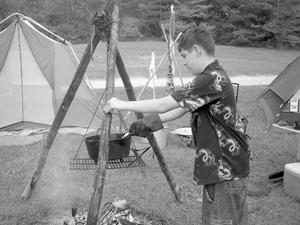 LUKENS CAMP RESORT A HIT! Above Joe Shepard prepares a stew for their noon meal.