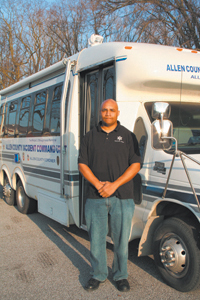 Detective Cornell Wiley stands in front of the Allen County Incident Command Unit. The unit gives officers a place at the crime scene where they can join together to compare notes and put together available information.