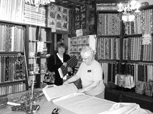Kathy Bogart cuts fabric while Georgi Schneider waits her turn.