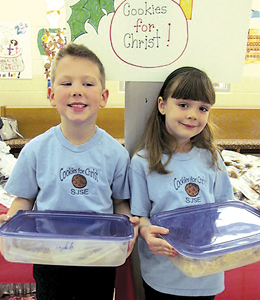 "First graders Parker Schimmele and Addeson Steffen put on a big smile as they brought in their cookies to sell at the annual ""Cookies for Christ"" sale."