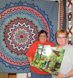 Sisters Peg Miller and Sharon Leatherman hold the last photo of their sister Carolyn in front of her folded star quilt.