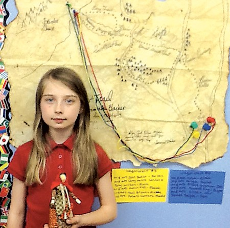 Fourth-grade Waynedale Elementary student DelaneyJensen, holds the traditional pioneer cornhusk doll created by Mary Lyons. The map the students made of the various western routes hangs behind her.