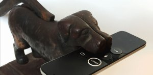 A statue of a dog that is holding a smart phone in its mouth.