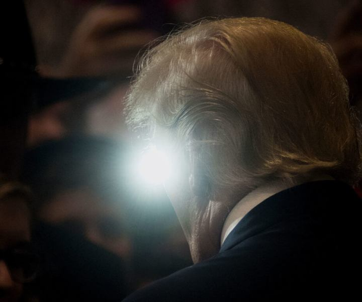 A light from the crowd is seen past Donald Trump, 2016 Republican presidential nominee, during a goodbye reception at the Westin Hotel in Cleveland, Ohio, U.S., on Friday, July 22, 2016. A day after accepting the Republican presidential nomination in a speech that signaled a more serious turn heading into the general election, Trump ripped into former primary competitor Ted Cruz, revisiting their ugly feud over Cruzs wife and father. Photographer: Ty Wright/Bloomberg via Getty Images
