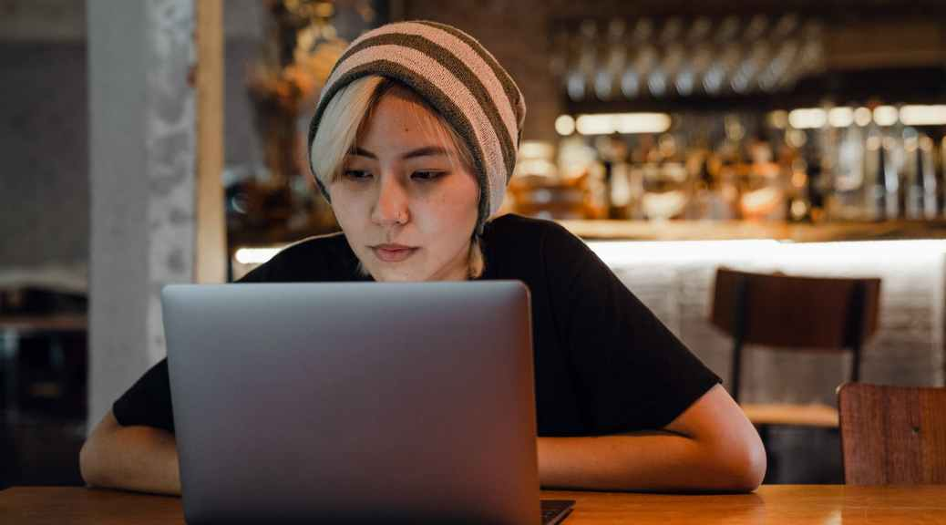 young woman watching movie on laptop in cafe