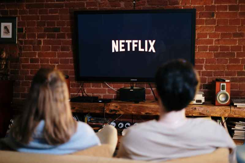man and woman sitting on a couch in front of a television