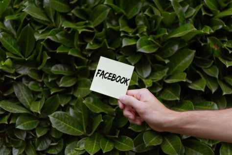 person holding a card with facebook text
