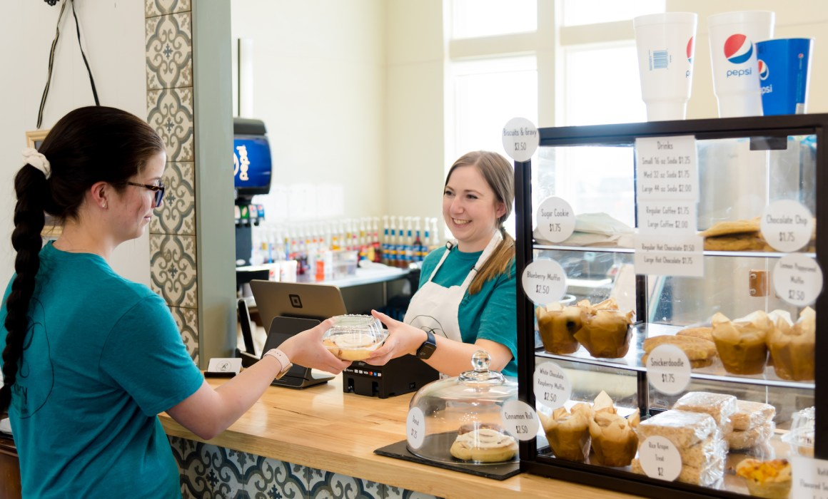 R Bakery owner selling a pastry from behind the counter | Utah Women-Owned Business Directory | Women's Business Center of Utah