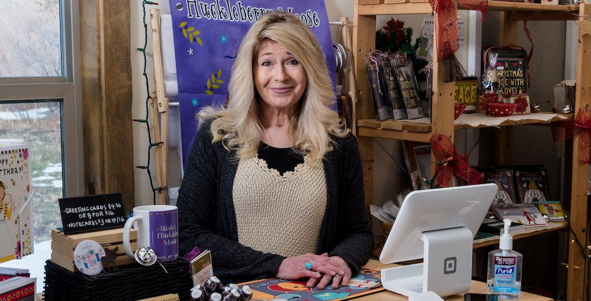 Huckleberry Moose Owner Lori standing in her store smiling | Utah Women-Owned Business Directory | Women's Business Center of Utah