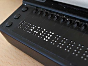 A refreshable braille device sits atop a table. The black, plastic display shows ten braille cells with white four feature brailled characters.