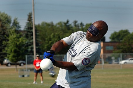 A man swings a bat at a ball while wearing a blindfold.