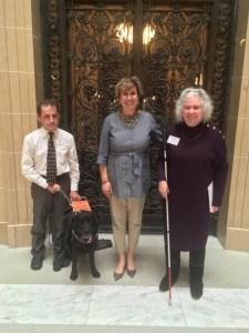 Two board members and a legislator stand inside the Wisconsin state capitol building. One board member has their service dog and one has a white cane.