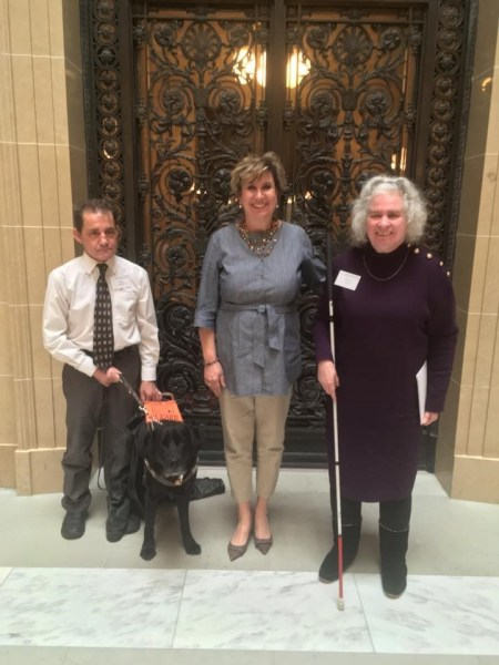 Three people stand in Capitol building. One has a white cane and one has a service dog.