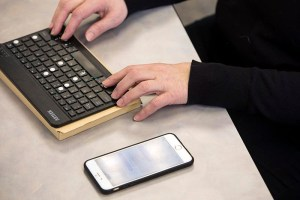 Two hands type on a keyboard with an iPhone sitting next to them.