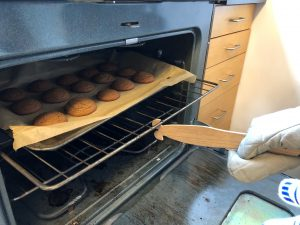 A push-pull oven ruler pulls out the oven rack holding 15 brown-colored cookies.