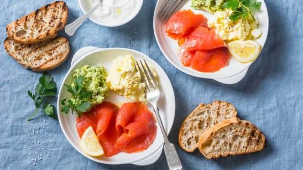 Two plates of eggs, salmon, lemon, bread and guacamole.