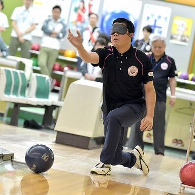 A man bowls while wearing a blindfold.