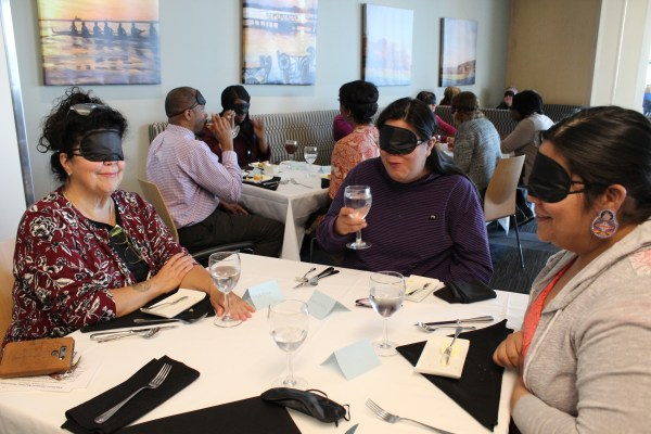 Three people sit at a dining table while wearing blindfolds.