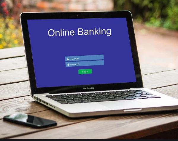 A laptop shows a screen that says Online Banking