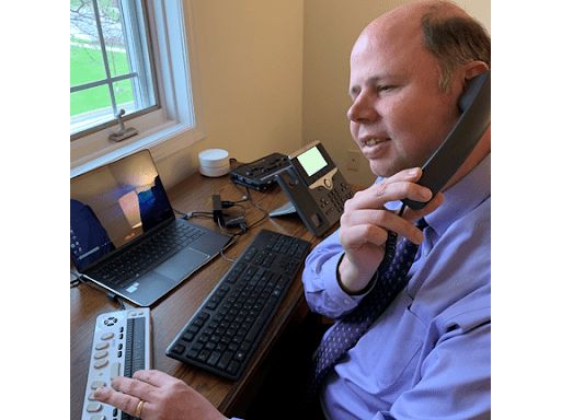A man on the phone with a braille keypad and keyboard in front of him.