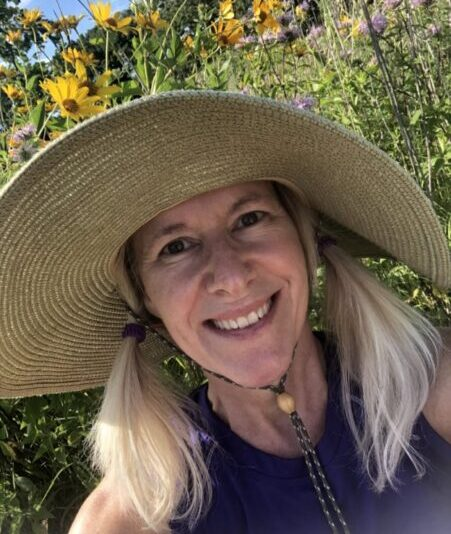 A woman with a large gardening hat smiles in a selfie with a garden behind her.