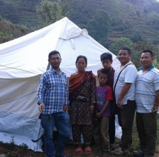 Pastors Uddav (left) and Silas (right) with a family who received this tent as shelter