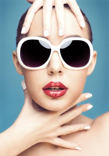 close up studio portrait of young beautiful woman wearing white sunglasses