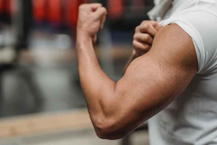 crop unrecognizable sportsman showing bicep in gym
