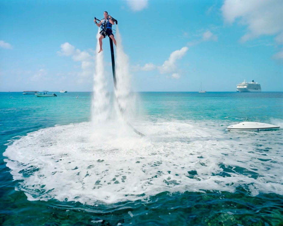 "An employee of ""Jetpack Cayman"" demonstrates this new watersport, now available on the island. A 2000cc motor pumps water up through the Jetpack, propelling the client out of the sea (359 USD for a 30-minute session). Mike Thalasinos, the owner of the company, remarks, ""The Jetpack is zero gravity, the Cayman are zero taxes, we are in the right place!"" Grand Cayman."