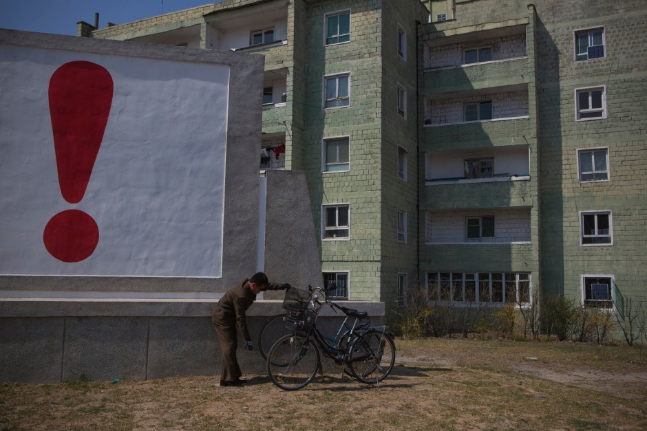 A North Korean man checks his bicycle next to a painted exclamation point on a propaganda billboard on Wednesday April 24, 2013 in Kaesong, North Korea, north of the demilitarized zone which separates the two Koreas.