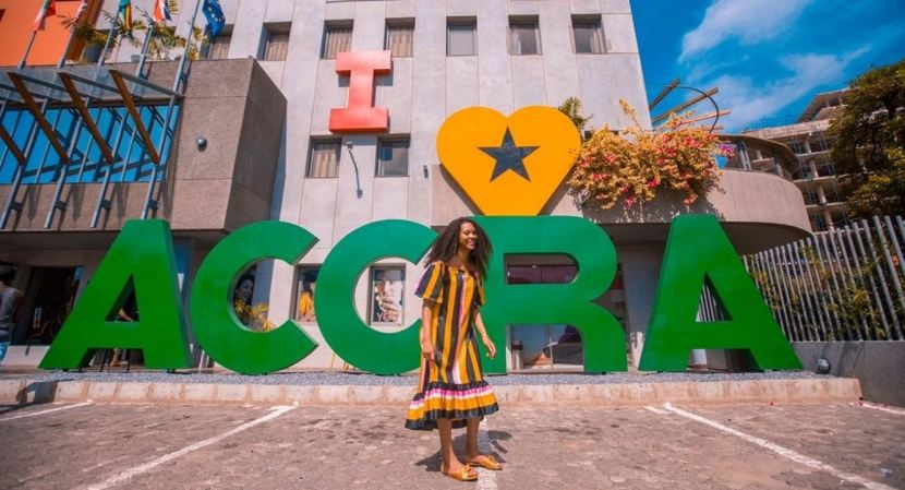 A woman in front of a landmark in Accra