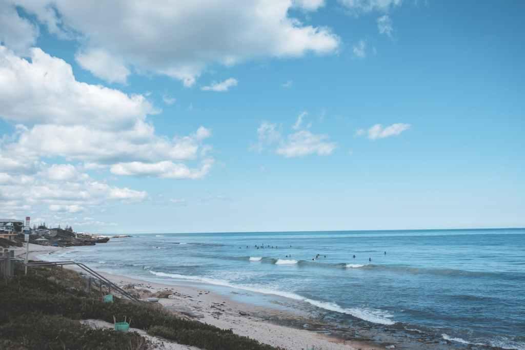 sandy beach near wavy sea water