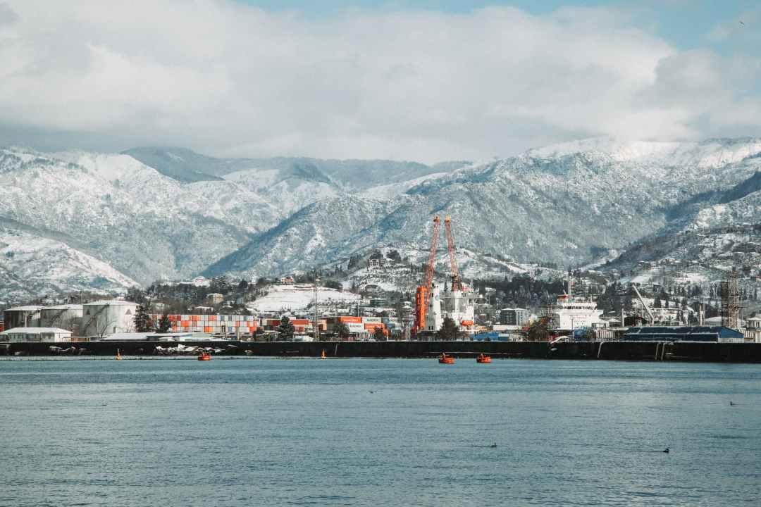 harbor near calm sea near snowy mountain