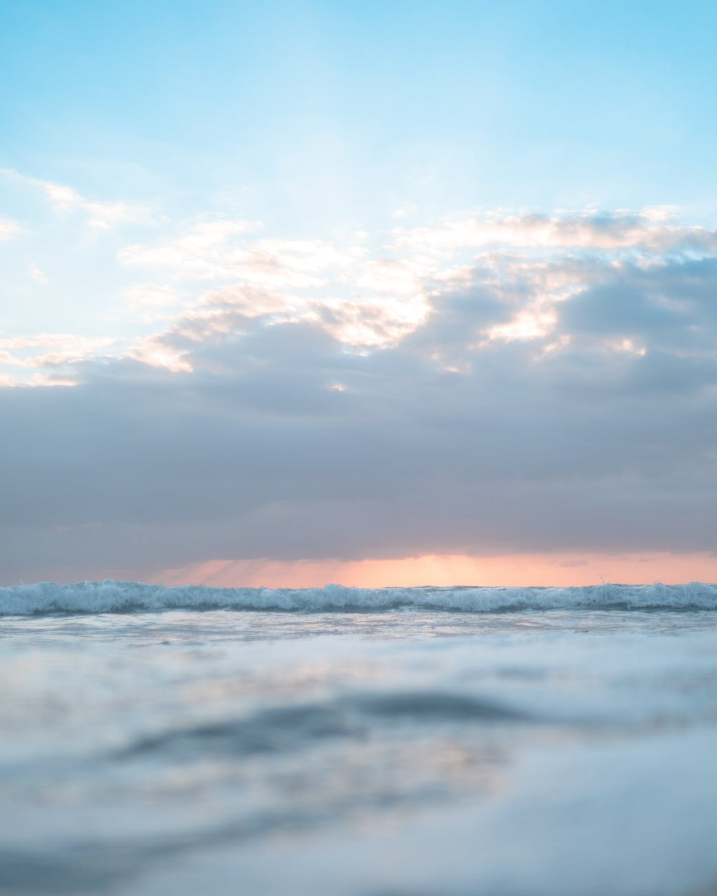 rippling wavy sea under blue cloudy sky