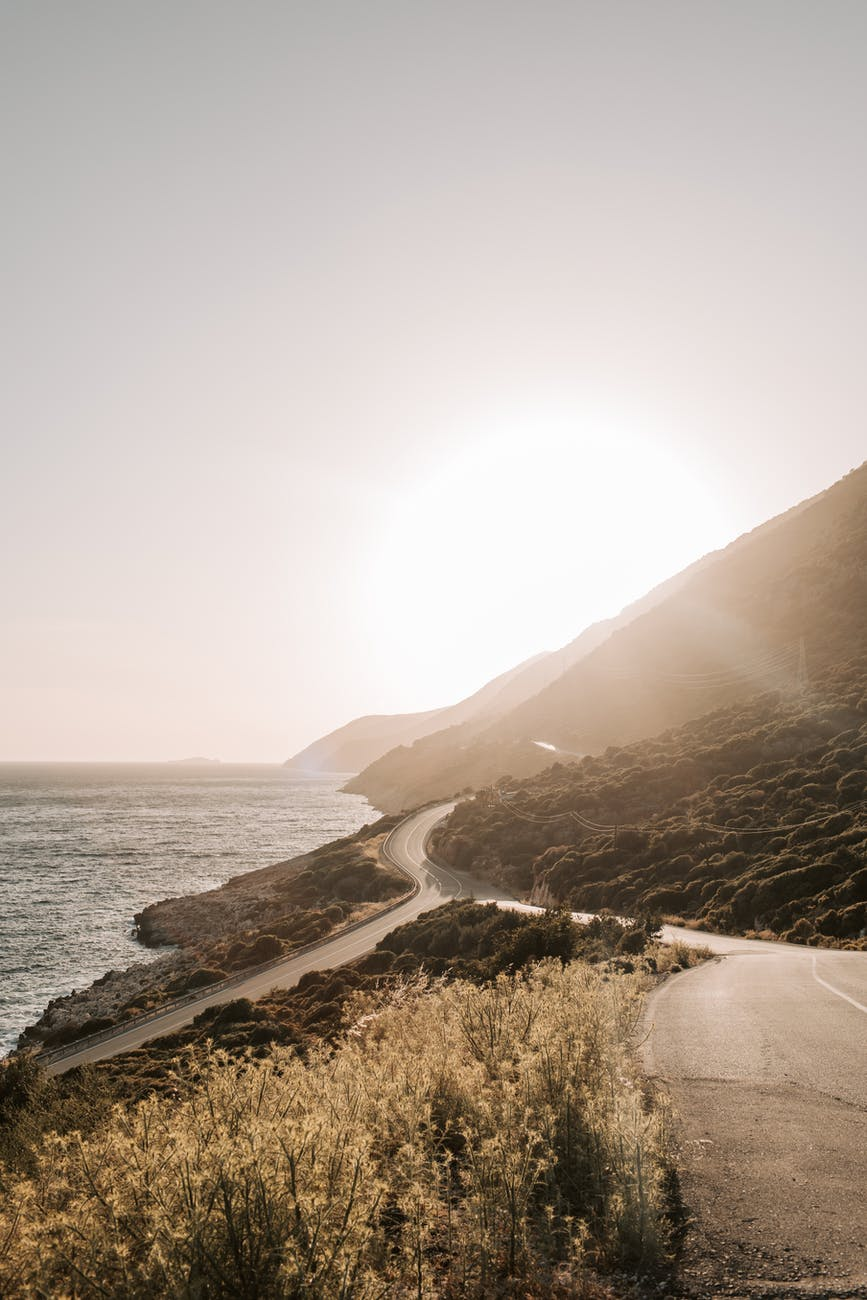 coastal road with view of sunset over the mountain