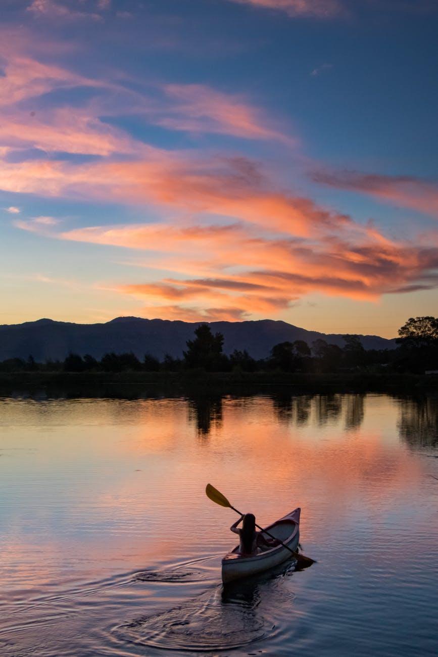 photo of person riding kayak during dawn