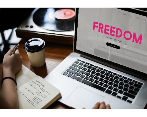 """A person is sitting at the desk and looking at their Laptop that displays the word """"FREEDOM"""" on the screen"""