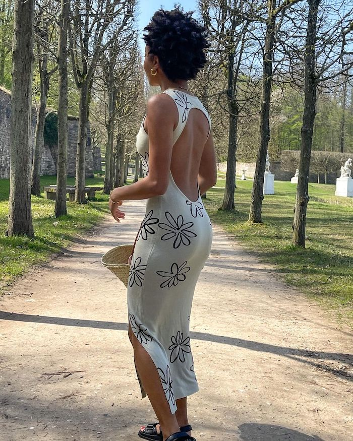 Ellie from @slipintostyle wearing a knitted white midi dress printed with black cartoon flowers, as she stands in a park