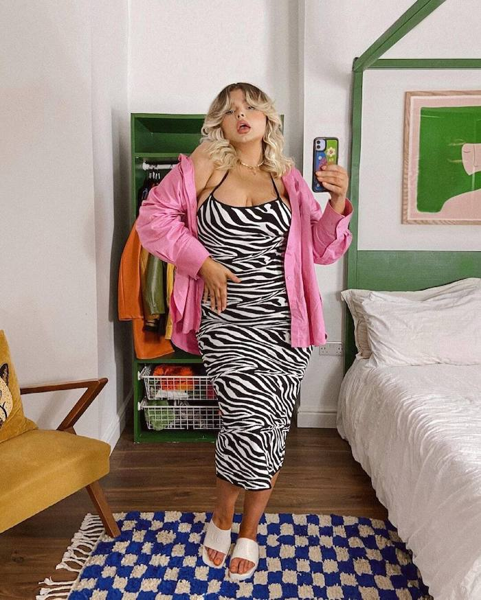 Influencer Francesca Perks wearing a zebra print slip dress with a pink shirt undone and white slides standing in front of her wardrobe taking a selfie in the mirror.