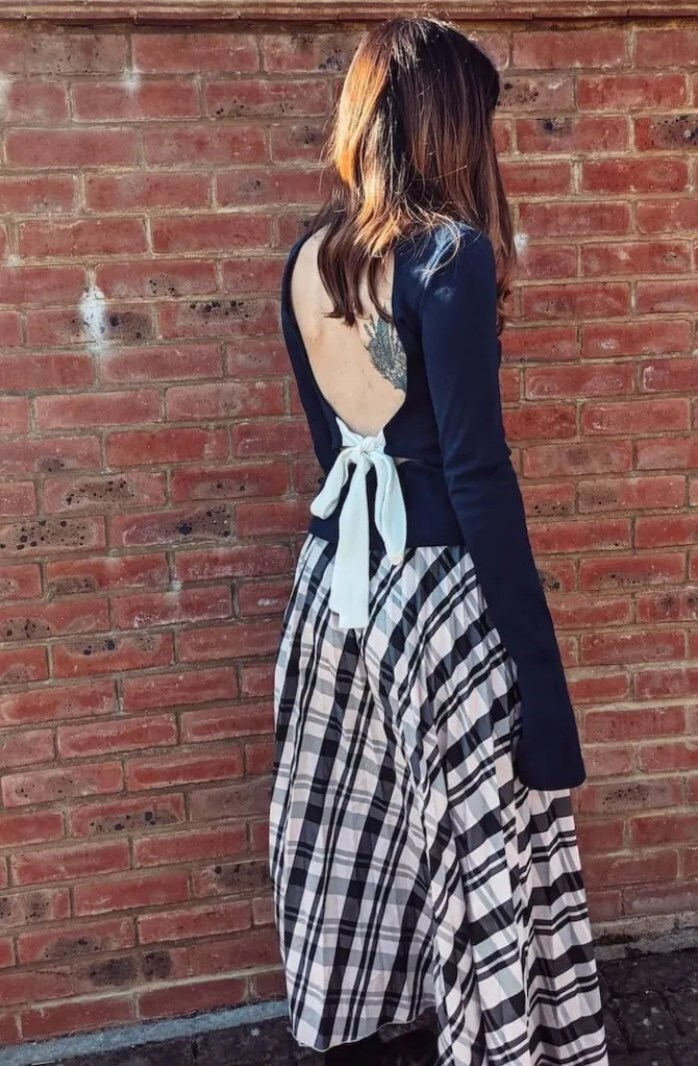 Founder and editor of Wear Next Daisy Jordan wears Fanfare Label navy backless jumper with white bow and a  light pink pleated check skirt as she stands in front of a red brick wall