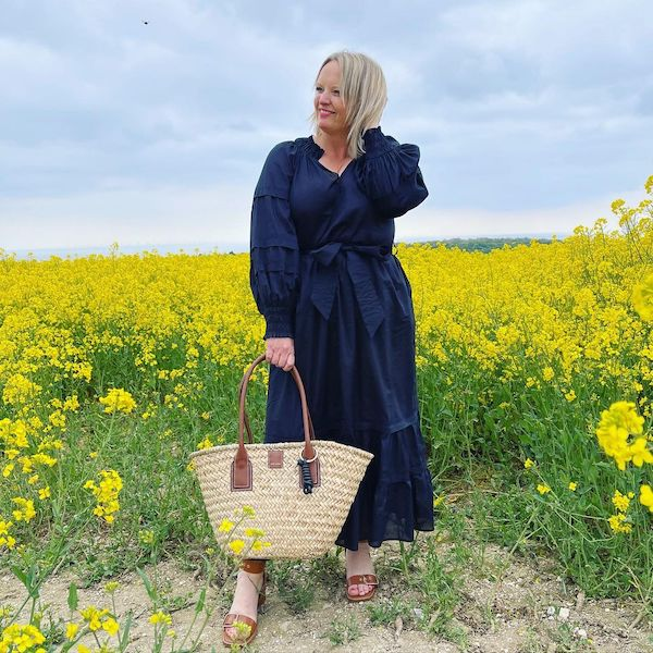@dress_loving_mama wearing a black long-sleeved midi dress in a rapeseed field holding a basket bag with leather tan handles.