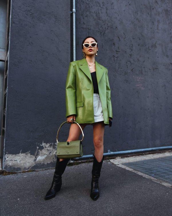 woman wears transitional green leather blazer at fashion week
