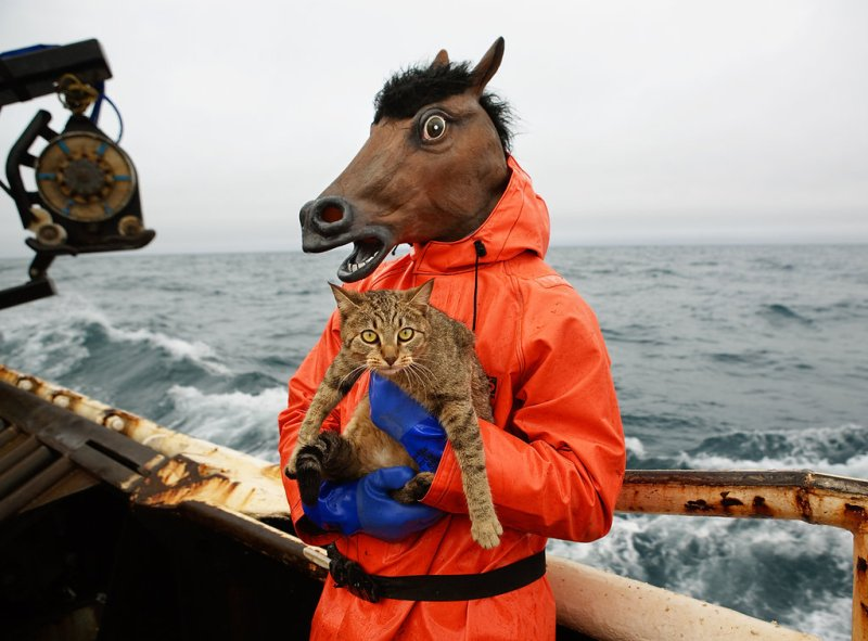 A crew member on the f/v Rollo tries out his Halloween costume and holds the boat Kitty.